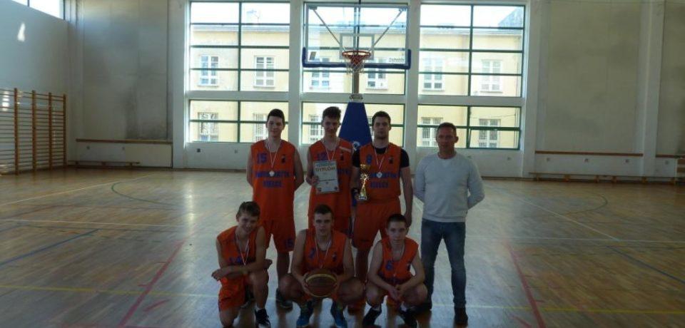 Szkolna drużyna koszykówki chłopców na podium.